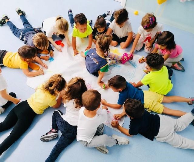Alumnos y alumnas pintando un mural en el suelo