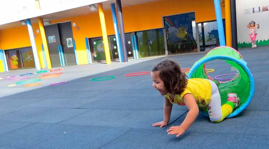 Alumna saliendo de un túnel de tela en el patio de la escuela infantil