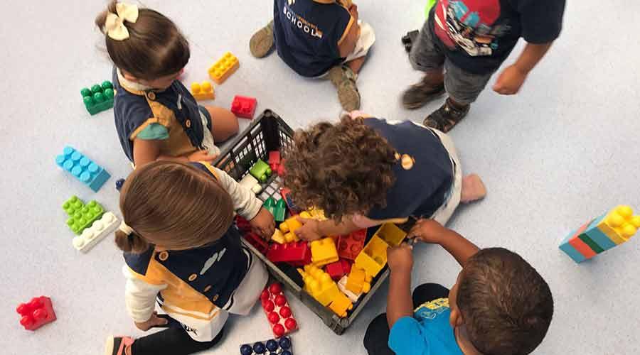 Grupo de niños y niñas jugando con piezas de colores en el suelo